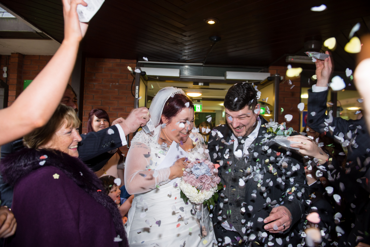 Bride and groom outside hotel with confetti